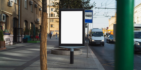 Billboard with digital screen for promoting ads. Sidewalk with pedestrians in busy city district and traffic on road at rush hour. People driving in cars and commuting to work taking public transport.