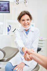Freundliche Zahnärztin begrüßt Patient mit Handschlag