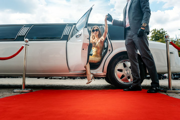 Driver helping VIP woman or star out of limo on red carpet