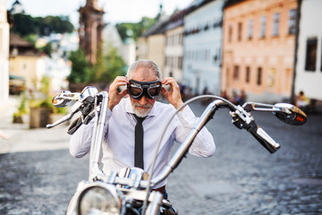 A senior businessman with motorbike in town, putting on goggles.