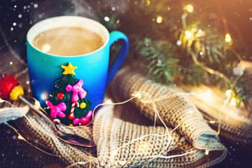 A Cup of hot cocoa in a Christmas mug on the background of Christmas garlands. Merry Christmas and happy New year. Selective focus.