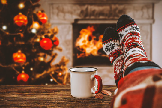 Woman legs with christmas socks and fireplace in home interiro