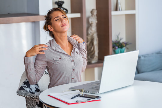 Young woman with hands holding her shoulder pain. Office syndrome and Health care concept. Business woman working with her laptop and with shoulder pain in the office