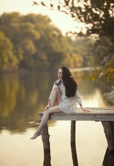 A young woman sits on the bridge by the water. Nymph girl at the lake.