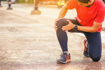 Runner man with sports running knee injury. Hands holding knee with painful.