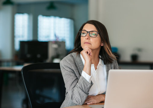 Businesswoman thinking about work while sitting at her office desk