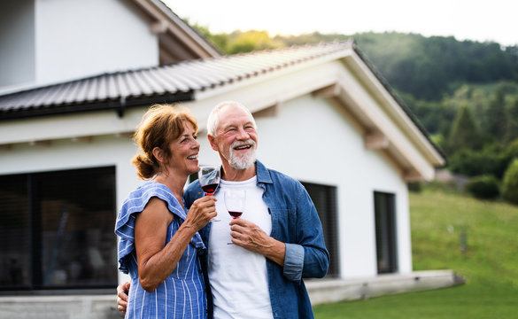 Portrait of senior couple with wine outdoors in backyard.