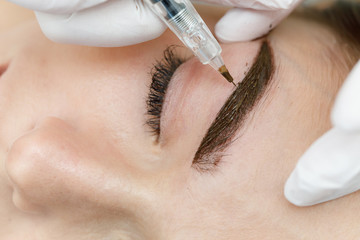 Permanent makeup, tattooing of eyebrows. Cosmetologist applying make up
