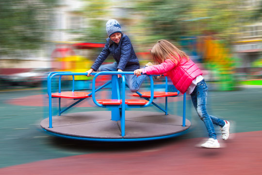 girl in pink jacket rolls boy on carousel in yard at playground outdoors