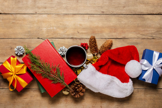 Cup with hot tea, Santa Claus hat, gift, Christmas decorations, books on a wooden background. Concept of Christmas, winter holidays, new year. Flat lay, top view