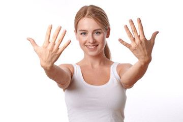 Smiling friendly young woman showing her hands with her fingers splayed towards the camera isolated on white
