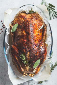 Christmas baked duck with herbs and spices in the oven dish, top view