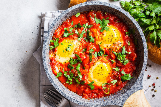 Traditional shakshuka in  pan. Fried eggs in tomato sauce with herbs, top view.