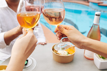 Close-up image of peope drinking rose wine when having fun at outdoor pool party