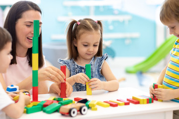 cute child girl with group of children and carer play with toys in the learning center