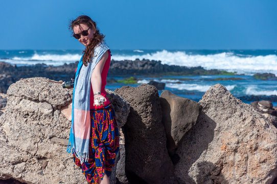 Handsome young woman with sunglasses showing seashells in her hand at the beach (Baia das Gatas, Sao Vicente Island, Cape Verde)