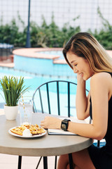 Positive young Vietnamese woman eating waffles and reading a book a cafe table by swimming pool