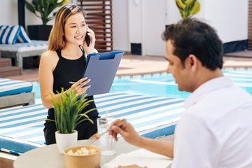 Smiling Vietnamese spa resort manager with document in hands making phone call