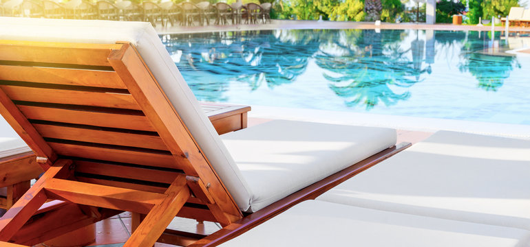 Deck chair and swimming pool in luxury resort