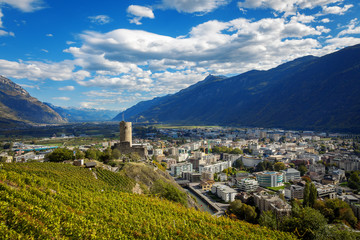 Terraced vineyards above Martigny in Valais Switzerland with medieval castle and Rhône valley.