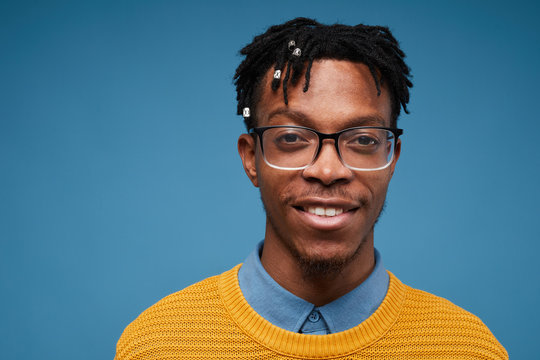 Head and shoulders portrait of contemporary African-American man smiling at camera while wearing bright knit sweater and posing against blue background, copy space