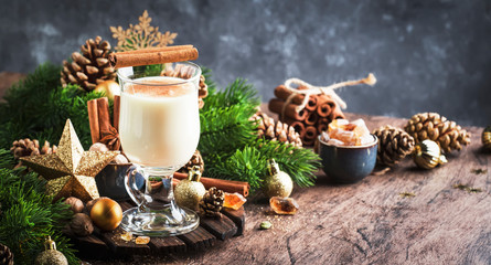 Christmas or New Year Eggnog alcoholic cocktail - hot winter drink with milk, eggs and rum, sprinkled with cinnamon and nutmeg in glass on gray background, copy space