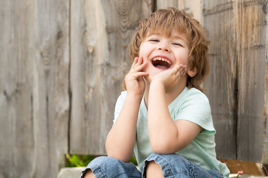 Happy boy. Cheerful childrens smile. Childrens happiness. A child sits in the garden near a wooden fence.