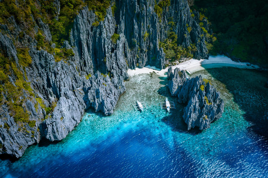 El Nido, Palawan, Philippines. Aerial above view of Secret hidden rocky lagoon beach with tourist banca boats in the cove surrounded by karst scenery