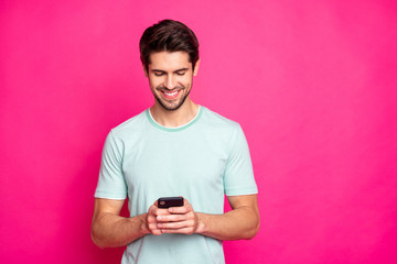 Photo of blogger guy holding telephone in hands checking subscribers toothy smiling wear casual outfit isolated vivid pink color background