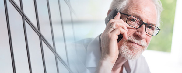 Senior businessman talking on mobile phone; panoramic banner