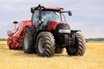Red Case IH Tractor and Seeder on Stubble Field. Illustrative Editorial content.
