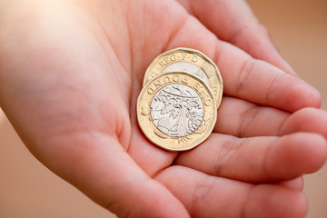 Kid hand showing money two pound coins on his hands,Child holding new British one pound on both hands, New pound coin, 2017 design