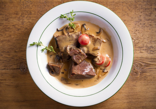 Braised beef cheeks in cream sauce with mushrooms and tomatoes in white bowl on wooden table. Overhead