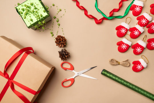 Christmas season. Wrapping New Year's gifts using gift wrapping, scissors, craft paper, cones, beads, small red mittens on a string. New Year 2020. Concept of New Year's gifts.