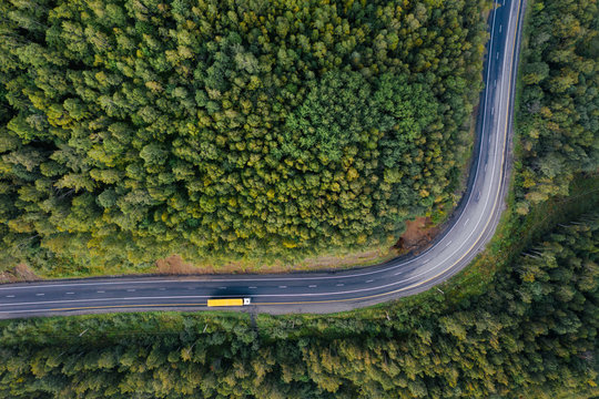 Top down aerial view of mountain road curve among green forest trees. Semi truck with cargo trailer on the highway. Transportation and natural scenery background with copy space