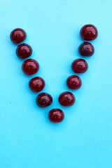 Letter V fresh cherry alphabet blue color flat lay