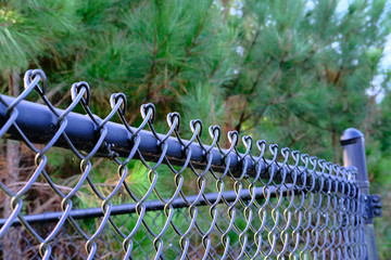 Light Falling on Top of Black Chain Link Fence