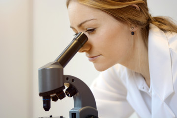 Doctor or scientist with microscope in laboratory