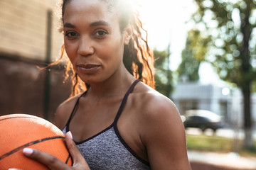 Attractive young african sportswoman playing basketball