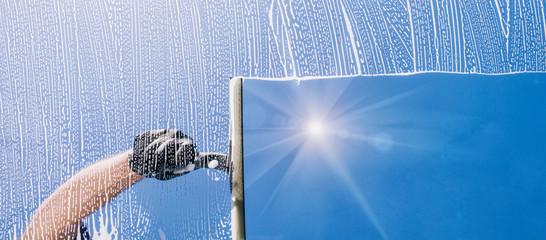 Fensterputzer putzt Fenster mit Schaum und Abzieher Panorama