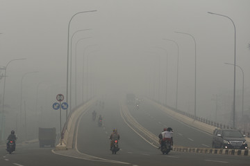 Motorists drive on the road as smoke covers the city due to the forest fire in Palembang
