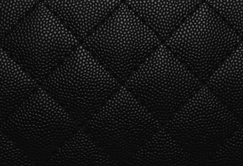 Close-up of artificial leather of elegance women's accessories fashion leather bag material texture pattern background in black color and grid pattern for used as backdrop or background.