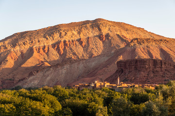 Moroccan berber village with mountains, river, desert, mountains and lush vegetation near sunrise