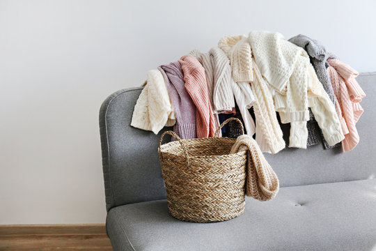 Categorizing winter laundry concept. A messy pile of kniwear lying on grey textile sofa. Bunch of unfolded sweaters prepeared for sorting. Close up copy space, background.