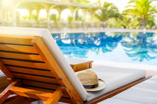 Lounger with sun hat and swimming pool in luxury resort