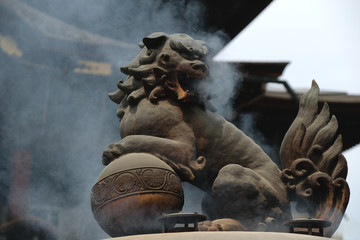 常香炉の上で煙を吐く獅子像