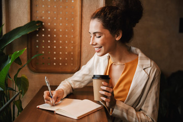 Woman indoors in cafe drinking coffee writing notes.