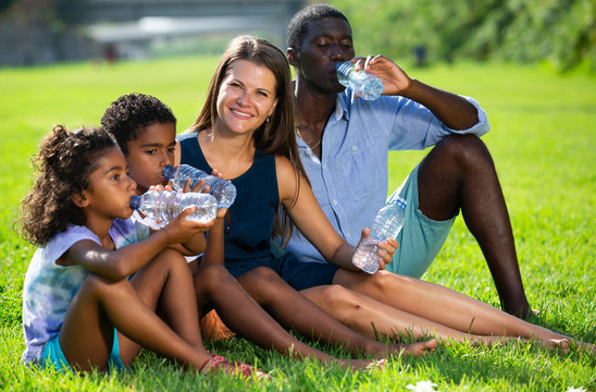 Family drinking water on green lawn
