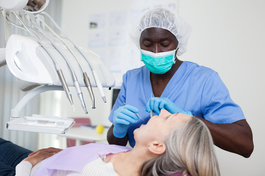 Mature female patient sitting in dental chair. Dentist is treating female patient