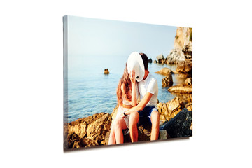 Canvas photo print isolated on white background. Colorful engagement photography with gallery wrap. Photo of kissing couple in love printed on glossy canvas